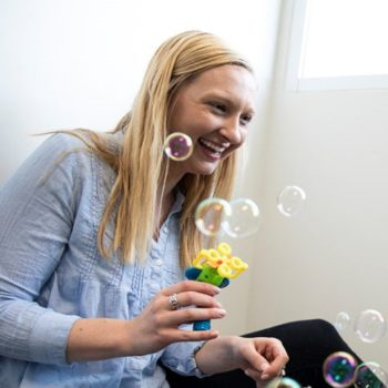 Emily Schworer blows bubbles and smiles