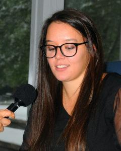 Mikayla Borton speaks into a mic